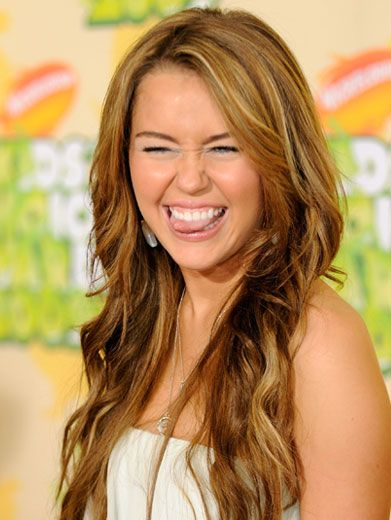 Nutty Nominee|Miley Cyrus can't help but flash a silly smile to the cameras on the KCA Orange Carpet.